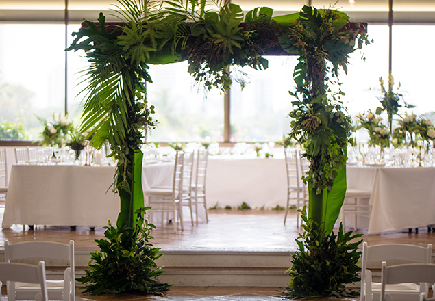 Timber arbour covered with greenery in front of white wedding tables