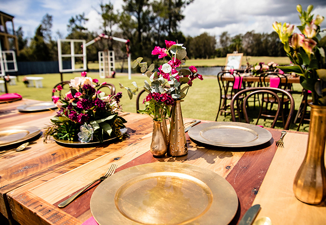Timber table with gold charger plates and Burgundy flowers in gold vases