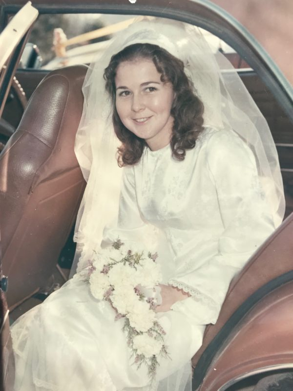 Lorraine in wedding dress sitting in back of car