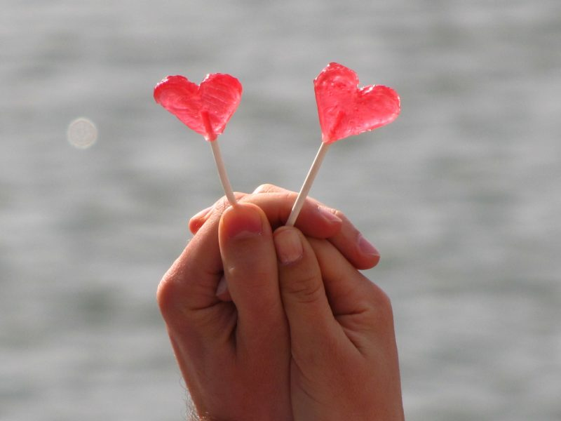 2 red love heart lollipop being held by two clasped hands
